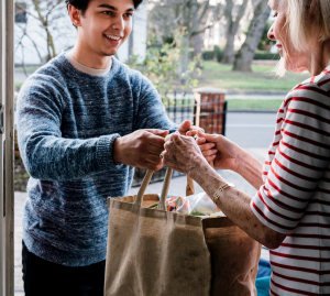 Volunteer drops off groceries to client